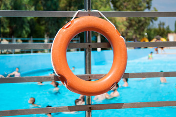 Red life buoy hanging in an open air swimming pool.