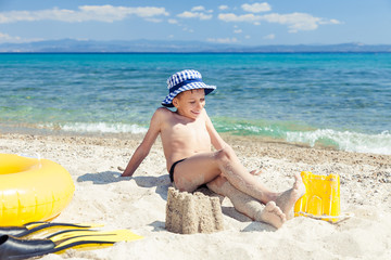 Funny child with panama sitting on beach with toys relaxing