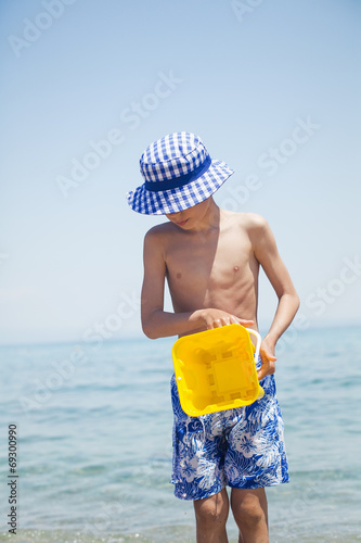 canvas print picture Child in swimmer shorts on beach holding toy bucket with water