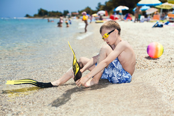 Cute boy diver sitting on beach putting on diver flippers