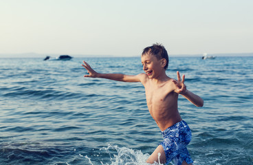 Funny little child playing in sea. Summer vacation concept.
