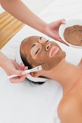 Smiling brunette getting a mud treatment facial