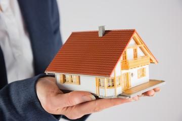 Businesswoman holding miniature model house