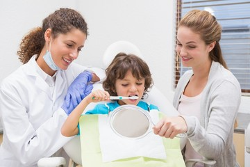 Pediatric dentist showing boy how to brush teeth