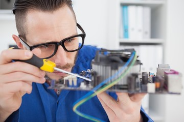 Computer engineer working on cpu with screwdriver
