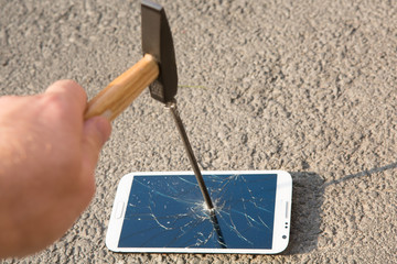 hammer smashing the screen of a smartphone