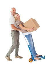 Happy couple having fun with trolley and moving box
