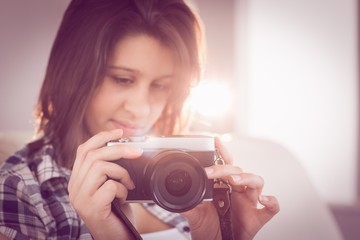 Pretty brunette looking at retro camera on couch