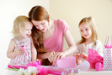 Mother and her two daughters wrapping a gift