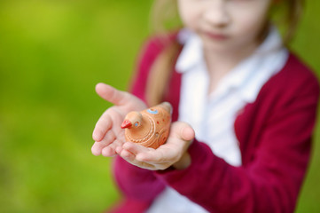 Adorable girl holding clay whistle