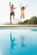 canvas print picture - Cheerful couple jumping into swimming pool