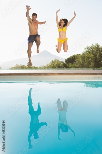 canvas print picture Cheerful couple jumping into swimming pool