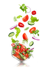 glass salad bowl in flight with vegetables: tomato, pepper, cucu