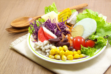 Salad and wood spoon, fork on cloth