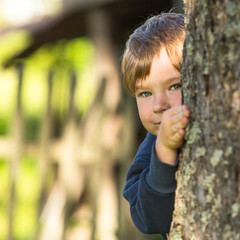 Little boy peeking out from behind a tree