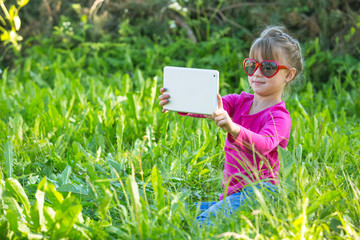 A little girl while taking a selfie at tablet PC in the park.