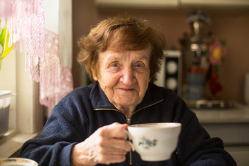 Close-up portrait of an elderly woman drinking tea at her home.