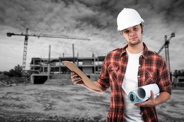 Portrait of confident young architect holding blueprints outside