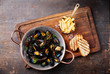 Mussels in copper cooking dish and french fries on dark wooden b - 69307544