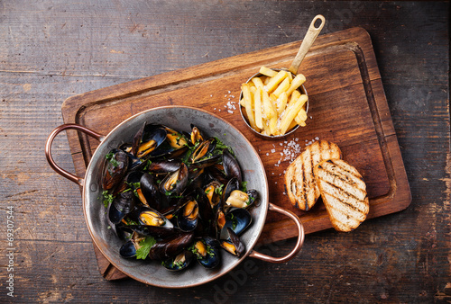 Aluminium Schaaldieren Mussels in copper cooking dish and french fries on dark wooden b