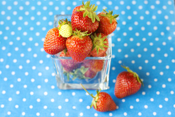 Strawberry in a glass bowl on the blue background