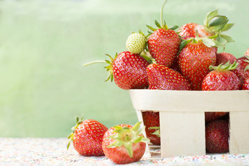 strawberries in a wooden basket on a floral background