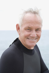 Man in wetsuit, smiling, portrait