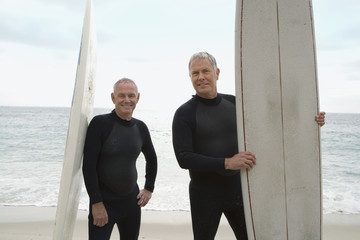 Male surfers in wetsuits with surfboards on beach, portrait