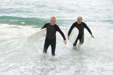 Male surfers in wetsuits in shallow water