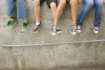 Small group of teenagers (11-15) sitting on wall, low section
