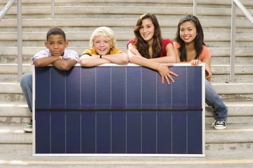 Small group of teenagers (11-15) with panel on steps outdoors, smiling, portrait