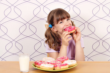hungry little girl eating sweet donuts