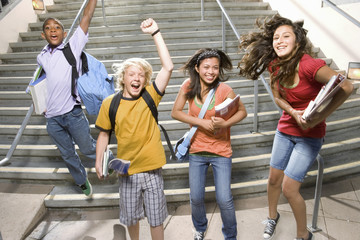 Small group of teenagers (11-15) jumping from steps outdoors, cheering, portrait