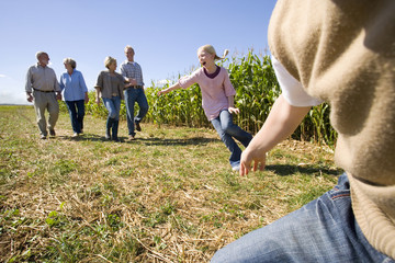 Family of three generations walking by corn field, low angle view
