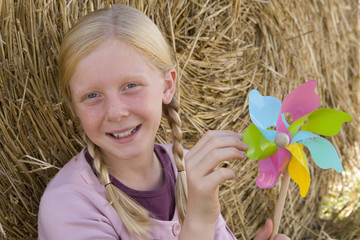 Girl (11-13) by bale of hay with pinwheel, smiling, portrait