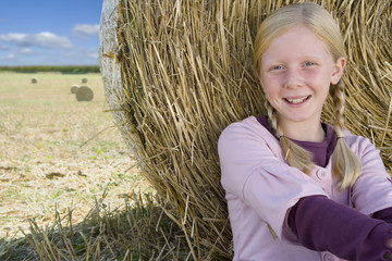 Girl (11-13) by hay bale in field, smiling, portrait