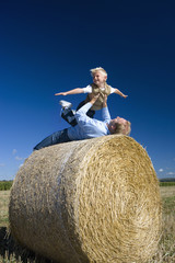 Father playing with son (7-9) on hay bale, low angle view