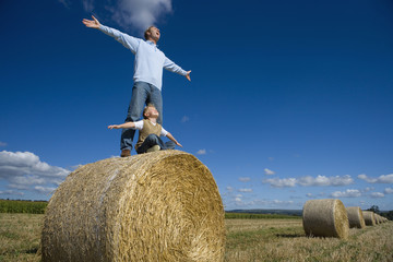 Father and son (7-9) playing on hay bale, arms outstretched, low angle view