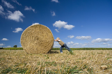 Boy (7-9) pushing bale of hay in field, low angle view