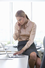 Businesswoman using laptop and talking on cell phone in office