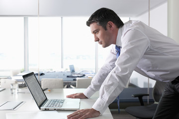 Businessman leaning on desk and looking at laptop in office