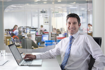 Portrait of smiling businessman with laptop in office