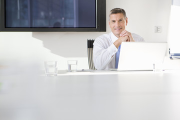 Portrait of smiling businessman using laptop in conference room
