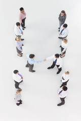 Businessmen shaking hands at center of co-workers in a row