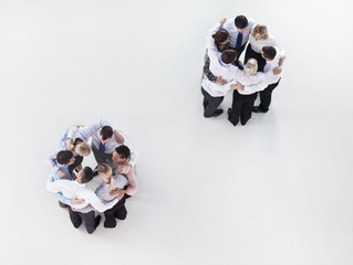 Two groups of business people talking in separate huddles