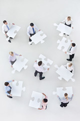 Business people holding large jigsaw pieces