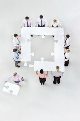 Businesswoman removing jigsaw piece from square formed by business people