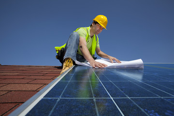 Engineer examining blueprints on solar panel on rooftop
