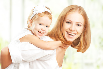 happy family: mother and baby daughter hugging and laughing