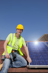 Portrait of smiling engineer on rooftop with solar panel and drill